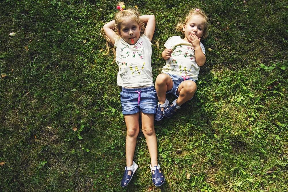Dziewczynki w butach dla dzieci typu barefoot leżą na trawie