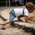 Dziecko idące na czworaka do piaskownicy w butach dla malucha typu barefoot